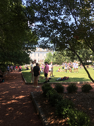 A small crowd gathers on Herty Field to watch the totality