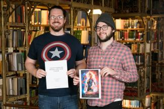 "Graduate students Ryan Hearn, left, and Joseph Rhyne hold the grammar guide and dictionary for the Torfan language and a poster for ""Captain Marvel."""